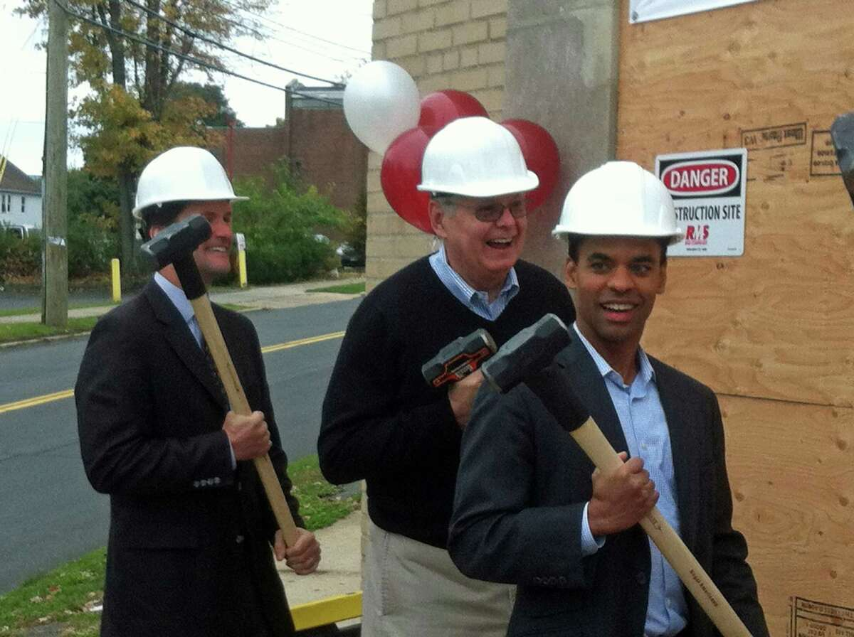 U.S. Rep. Jim Himes, Stamford Mayor David Martin and NBC Sports Vice President Rob Simmelkjaer swing sledge hammers in a ceremonial groundbreaking for a new home of the New Covenant House soup kitchen.