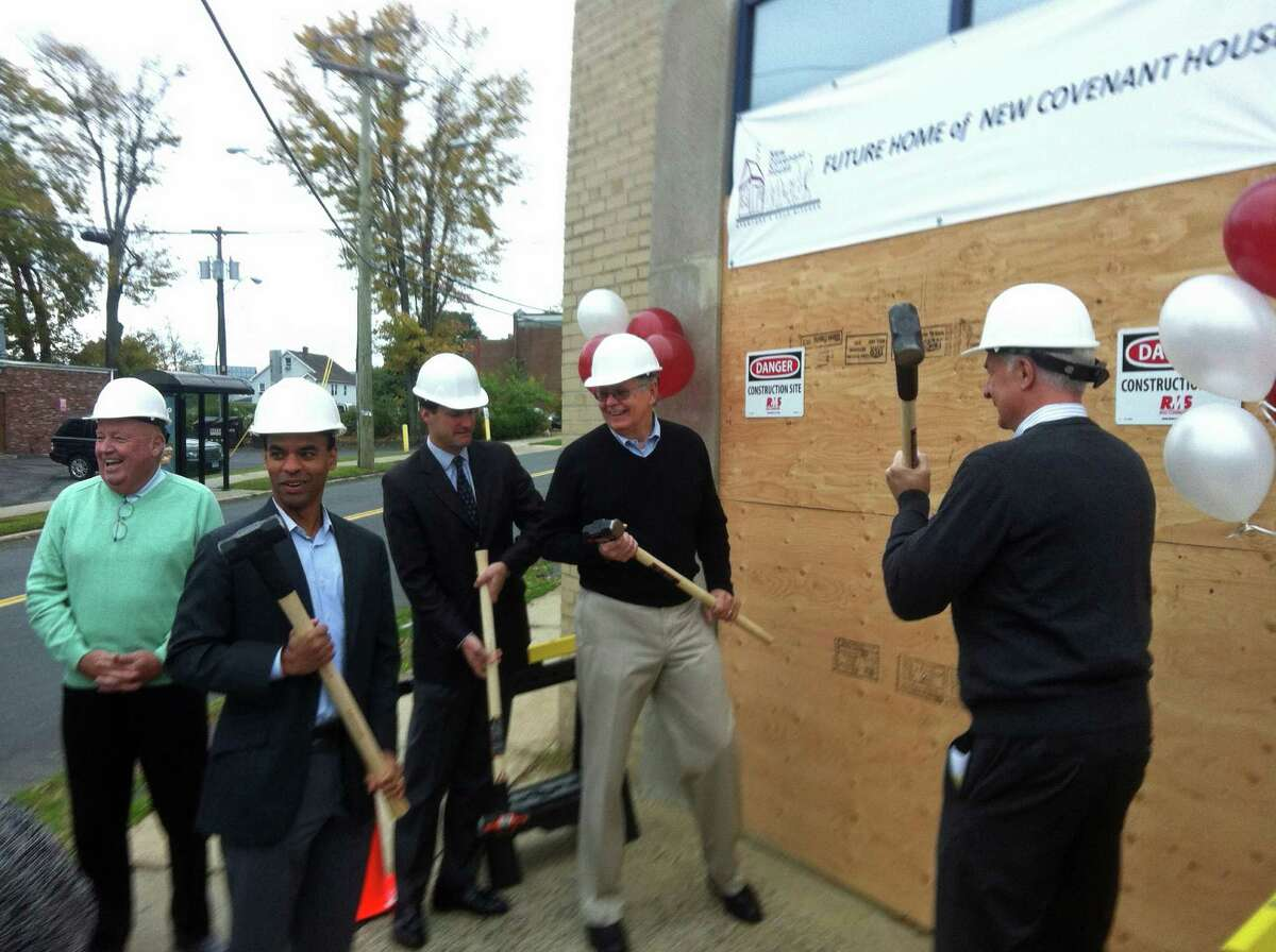 Catholic Charities of Fairfield County CEO Al Barber, left, NBC Sports Vice President Rob Simmelkjaer, U.S. Rep. Jim Himes, Stamford Mayor David Martin and New Covenant House advisory board Chairman Paul Harinstein swing sledge hammers in a ceremonial groundbreaking for a new home of the New Covenant House soup kitchen.