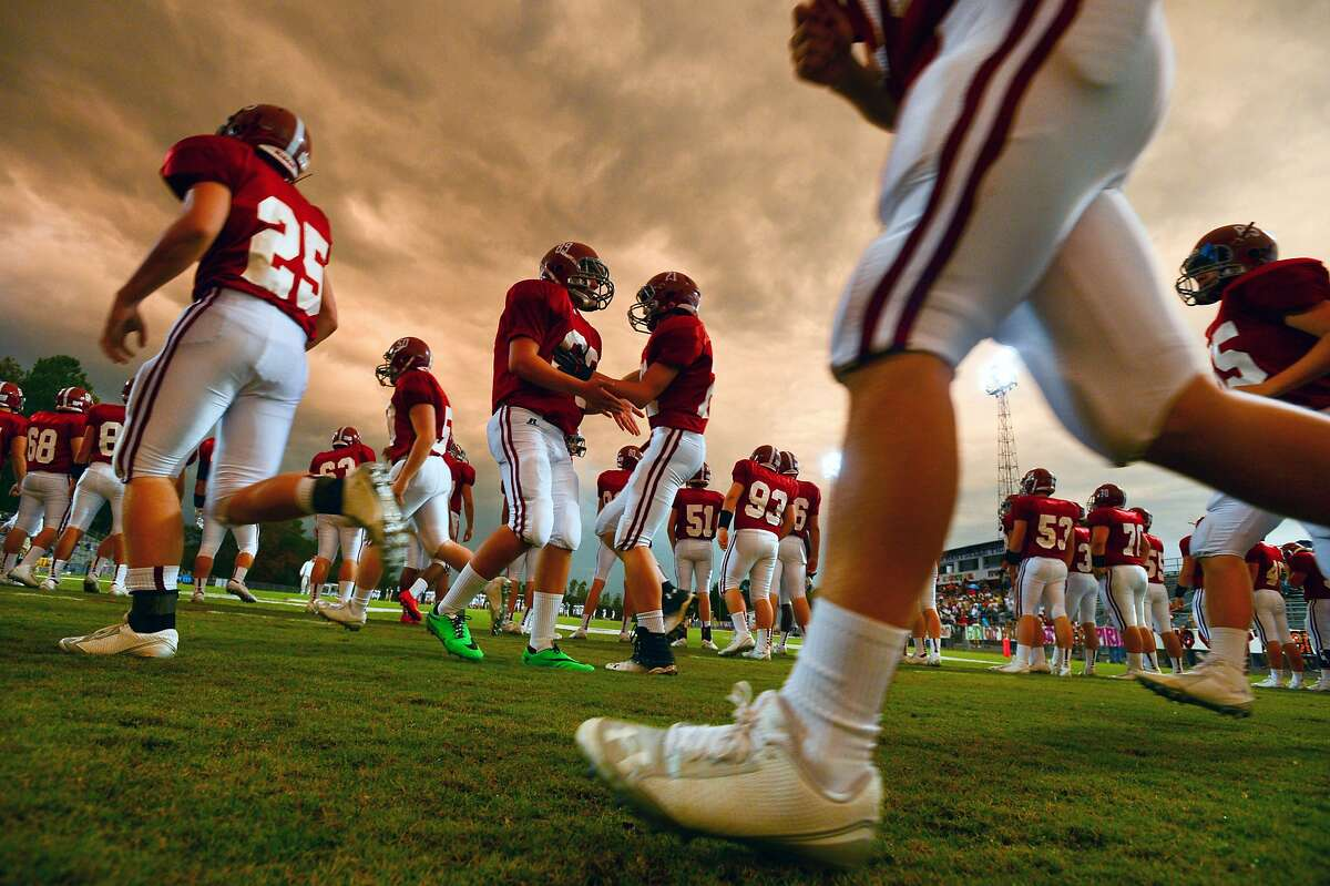 AS A THUNDERSTORM PASSES to the south, Hartselle High School football players warm up before a game against Cullman in Hartselle, Ala.