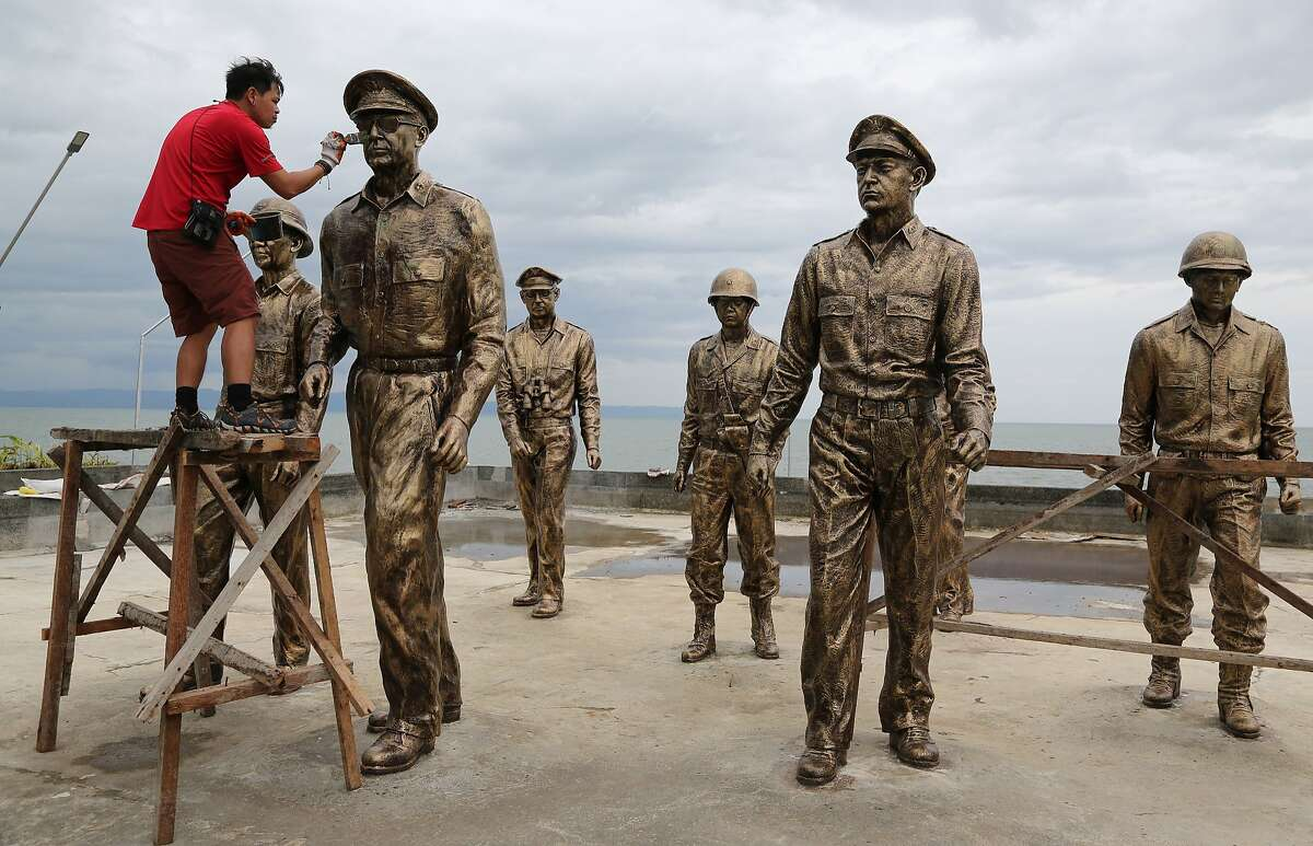 I SHALL REFURBISH: Filipino materials conservator Rommel Aquino restores the statue of U.S. Gen. Douglas MacArthur at the Leyte Landing Memorial in Palo, Leyte province. The statues were damaged when Typhoon Haiyan struck the Philippine province last year.