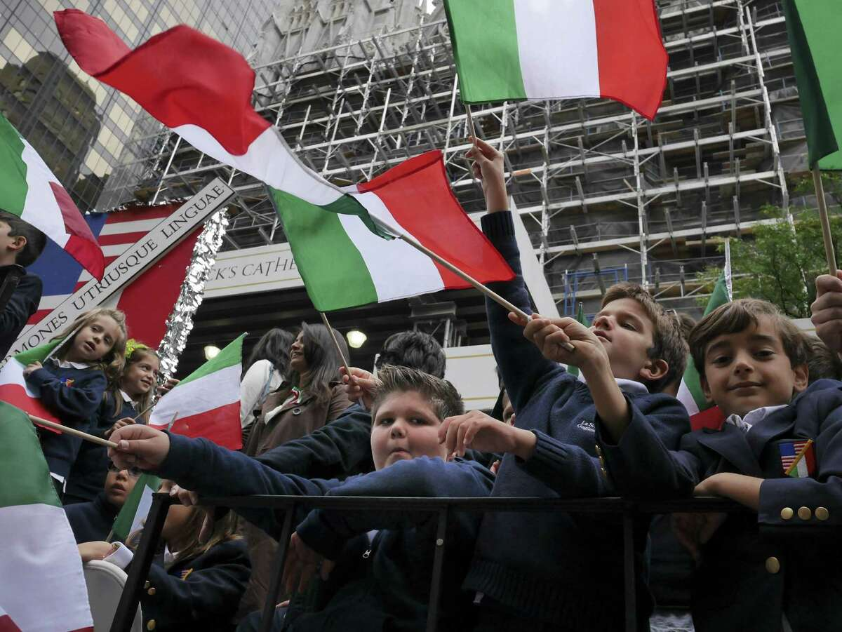 School children wave Italian flags on a float in the Columbus Day parade in New York, Monday, Oct. 13, 2014. The parade is organized by the Columbus Citizens Foundation, and is billed as the world's largest celebration of Italian-American heritage and culture. (AP Photo/Seth Wenig) ORG XMIT: NYSW110