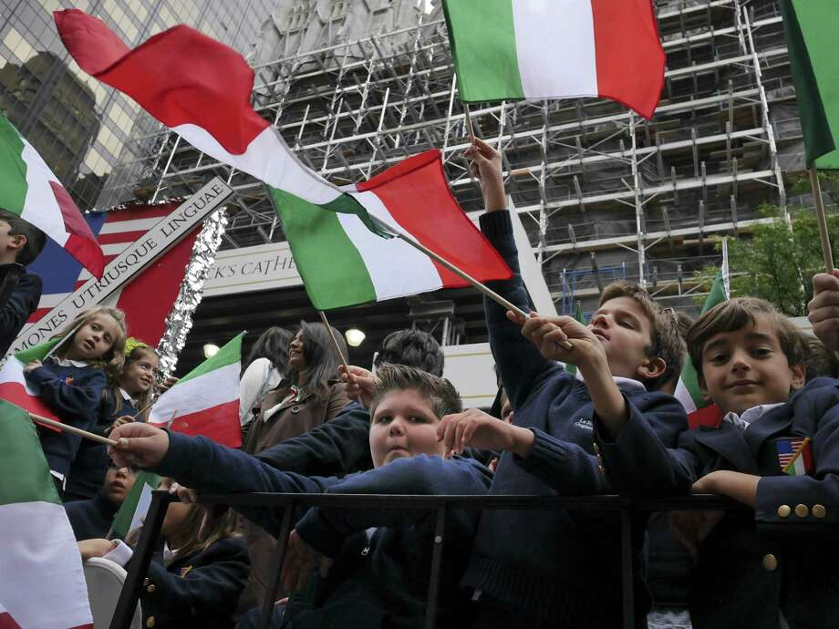 School children wave Italian flags on a float in the Columbus Day parade in New York, Monday, Oct. 13, 2014. The parade is organized by the Columbus Citizens Foundation, and is billed as the world's largest celebration of Italian-American heritage and culture. (AP Photo/Seth Wenig) ORG XMIT: NYSW110 Photo: Seth Wenig, AP / AP