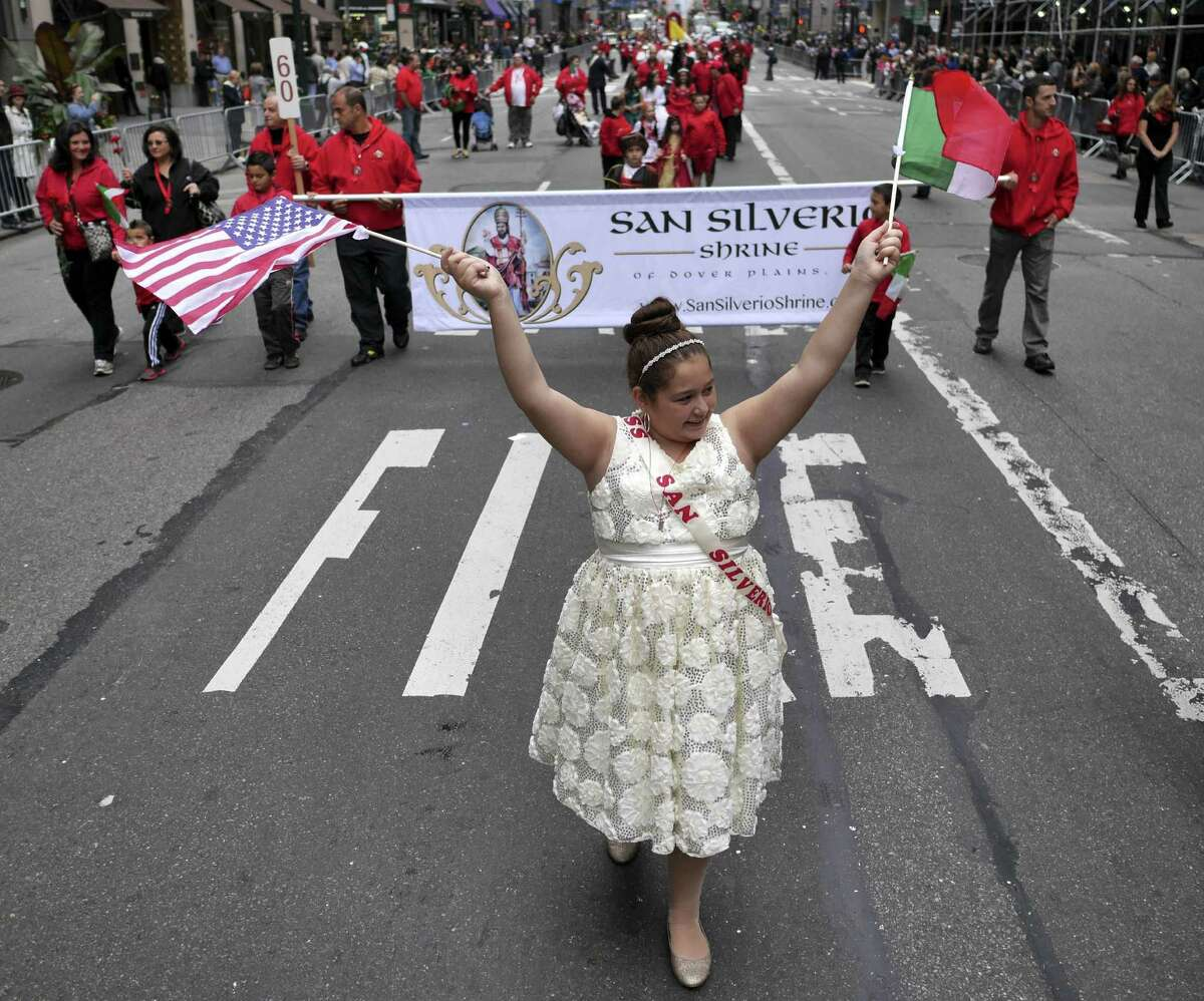 Victoria Pitaro, 11, waves flags as she marches in the Columbus Day parade in New York, Monday, Oct. 13, 2014. The parade is organized by the Columbus Citizens Foundation, and is billed as the world's largest celebration of Italian-American heritage and culture. (AP Photo/Seth Wenig) ORG XMIT: NYSW112