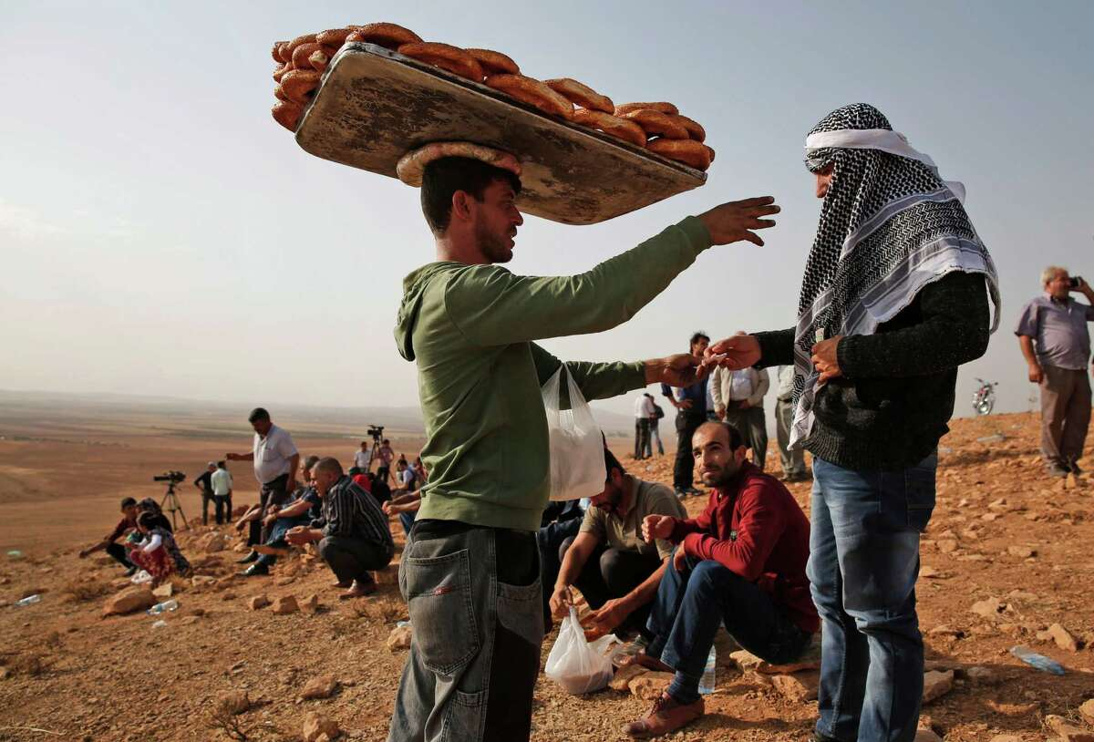 A vendor sells bread on a hilltop on the outskirts of Suruc, at the Turkey-Syria border, as people gather to watch fighting between Syrian Kurds and the militants of Islamic State group in Kobani, Syria, Monday, Oct. 13, 2014. Kobani, also known as Ayn Arab, and its surrounding areas, has been under assault by extremists of the Islamic State group since mid-September and is being defended by Kurdish fighters.