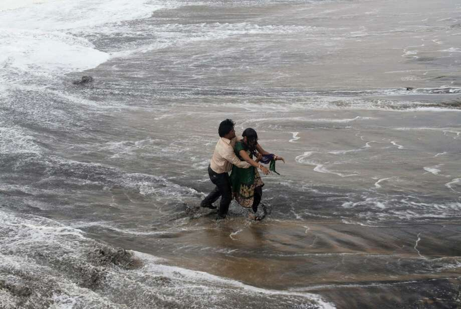 A man rescues a woman who was caught in strong tidal waves Sunday as a cyclone bore down on the coast of the Bay of Bengal in the town of Gopalpur in the state of Orissa. Photo: Biswaranjan Rout / Associated Press / AP