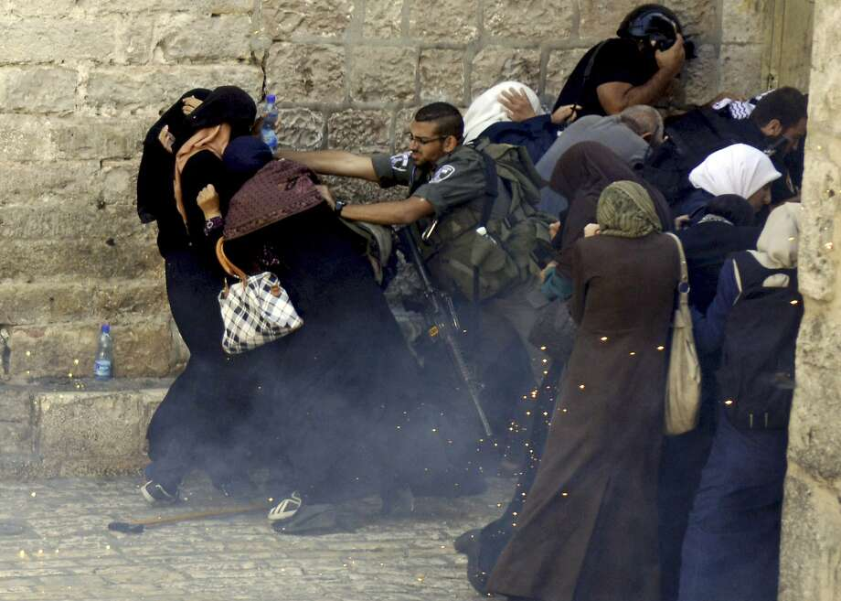 Israeli border policeman push Palestinian women during clashes in the Old City of Jerusalem, Monday Oct. 13, 2014. Israeli police clashed with young Palestinian protesters on Monday demonstrating against Jews visiting the Al-Aqsa Mosque compound, Islam's third holiest site, a spokeswoman said. Photo: Mahmoud Illean, Associated Press