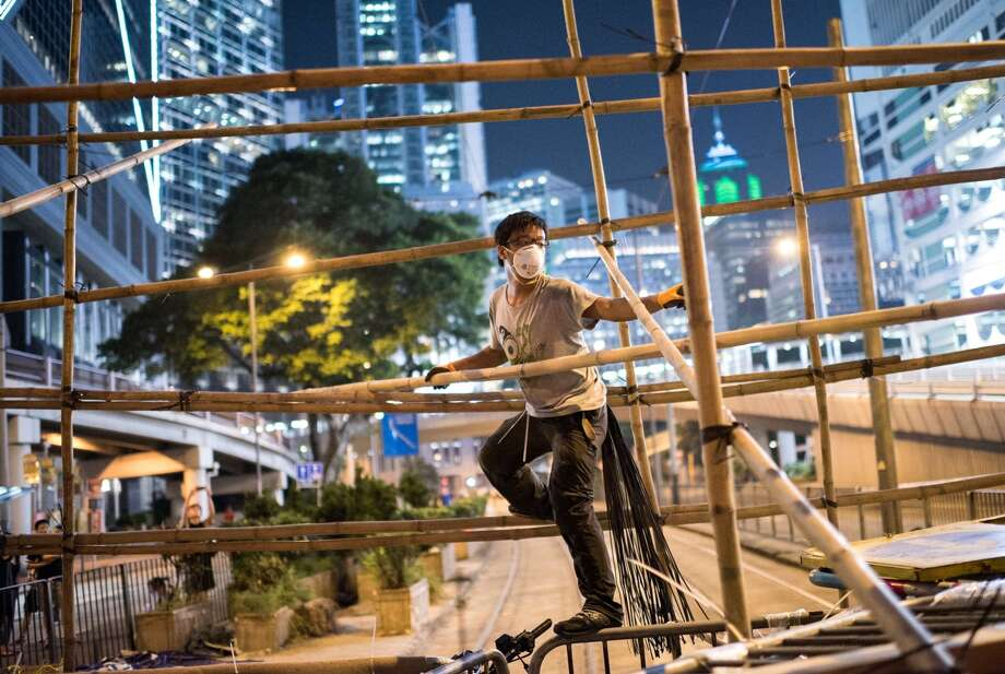 A pro-democracy protester uses bamboo to strengthen a barricade blocking a major road in Hong Kong after mobs of masked men tore flimsier barriers down and clashed with police. Photo: ALEX OGLE / AFP/Getty Images / AFP