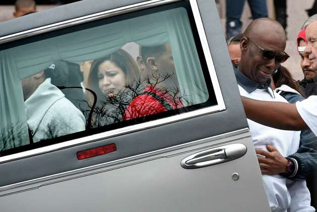 The woman identified as the  fiance of the deceased is framed by the rear door window of the hearse that carries the casket of Jorge A. Falu-Garcia before it leaves the Cathedral of the Immaculate Conception after a funeral ceremony Monday, Oct. 13, 2014, in Albany, N.Y.  To the right a pall bearer is overcome by emotion as the casket is prepared for it final journey to the cemetery. Falu-Garcia was shot and killed  October 2nd on 1st Street in Albany.   (Skip Dickstein/Times Union) Photo: SKIP DICKSTEIN / 10028970A