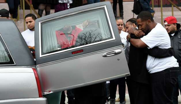 Two people embrace as the casket carrying the remains of Jorge A. Falu-Garcia sits in the hearse outside the Cathedral of the Immaculate Conception after a funeral ceremony Monday, Oct. 13, 2014, in Albany, N.Y.  Falu-Garcia was shot and killed  October 2nd on 1st Street in Albany.   (Skip Dickstein/Times Union) Photo: SKIP DICKSTEIN / 10028970A
