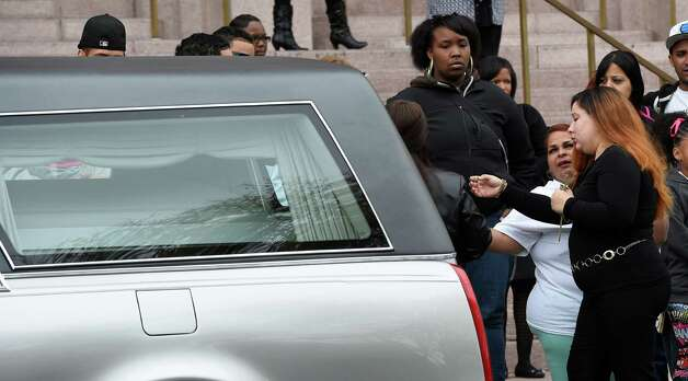 The woman identified as the fiance of the deceased looks over at the casket carrying the remains of Jorge A. Falu-Garcia in the hearse before it leaves the Cathedral of the Immaculate Conception after a funeral ceremony Monday, Oct. 13, 2014, in Albany, N.Y.  Falu-Garcia was shot and killed October 2nd on 1st Street in Albany.   (Skip Dickstein/Times Union) Photo: SKIP DICKSTEIN / 10028970A