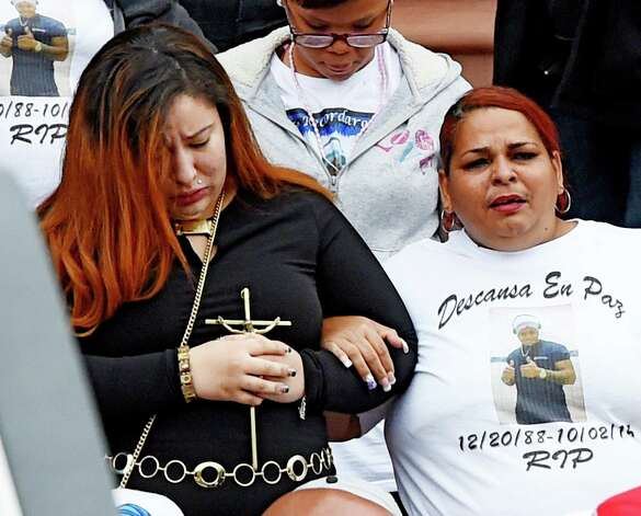 The woman identified as his fiance carries a crucifix, left, as the casket carrying the remains of Jorge A. Falu-Garcia as it leaves the Cathedral of the Immaculate Conception after a funeral ceremony Monday, Oct. 13, 2014 in Albany, N.Y.  Falu-Garcia was shot and killed  October 2nd on 1st Street in Albany.   (Skip Dickstein/Times Union) Photo: SKIP DICKSTEIN / 10028970A
