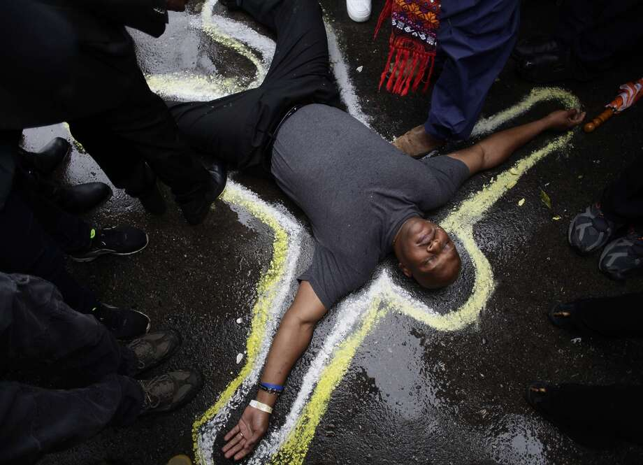 Pastor Charles Burton lies inside a chalk outline near the Ferguson police station to protest the shooting deaths of Michael Brown and other black men at the hands of police. Photo: JOSHUA LOTT / AFP/Getty Images / AFP