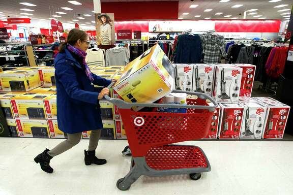 In a scene from Black Friday past, Judy Einbinder walks past vacuums after picking up a microwave at Target last Nov. 29 in Houston. Researchers say to expect more sales and promotions this year, even as holiday spending is forecast to rise 4 percent. (Cody Duty / Houston Chronicle)