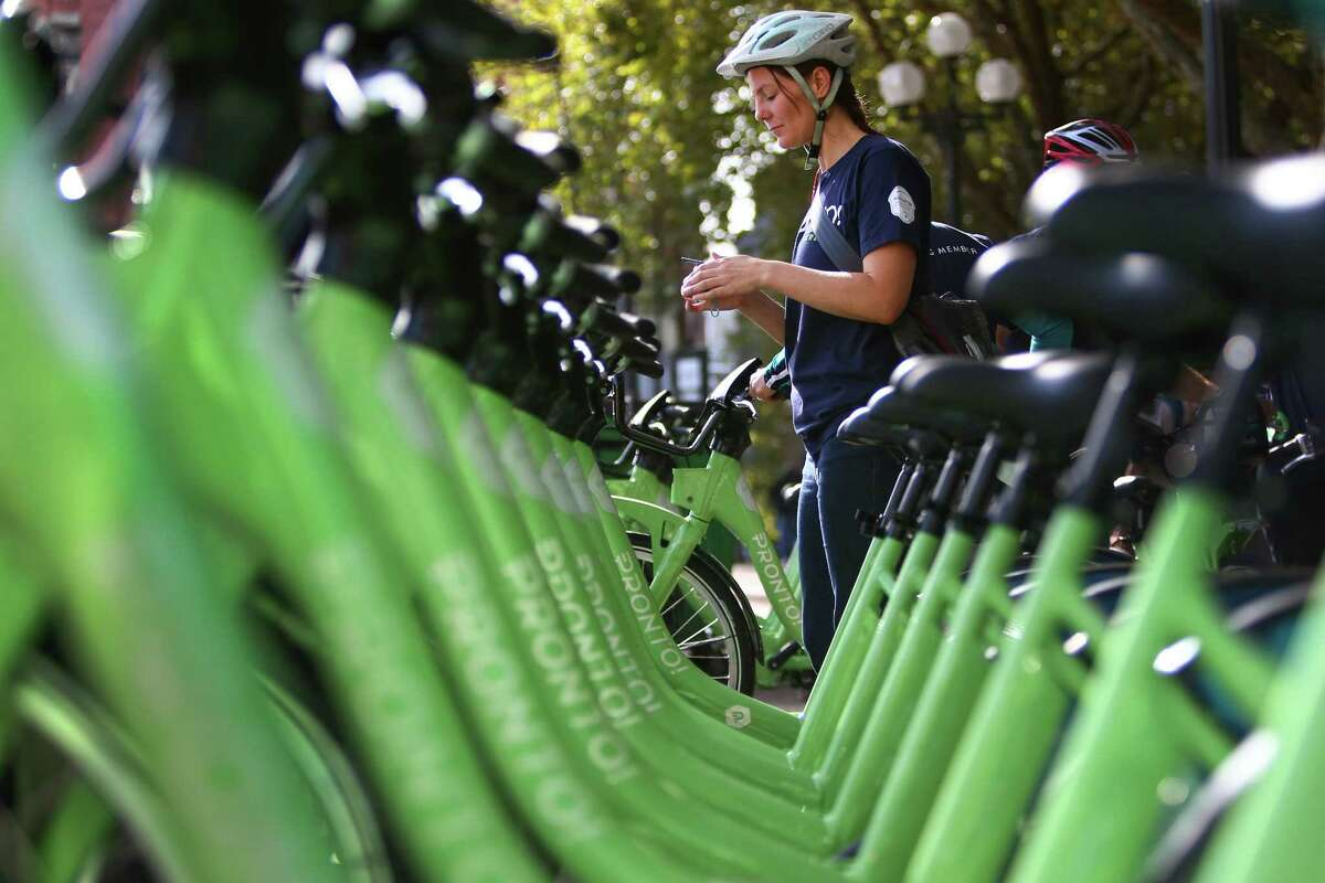 A rider participating in an inaugural ride prepares to check out a bike from Pronto Cycle Share as the program is launched in Seattle on Monday, October 13, 2014. The program will have 500 bicycles available for rent at 50 stations mostly in the core of Seattle.