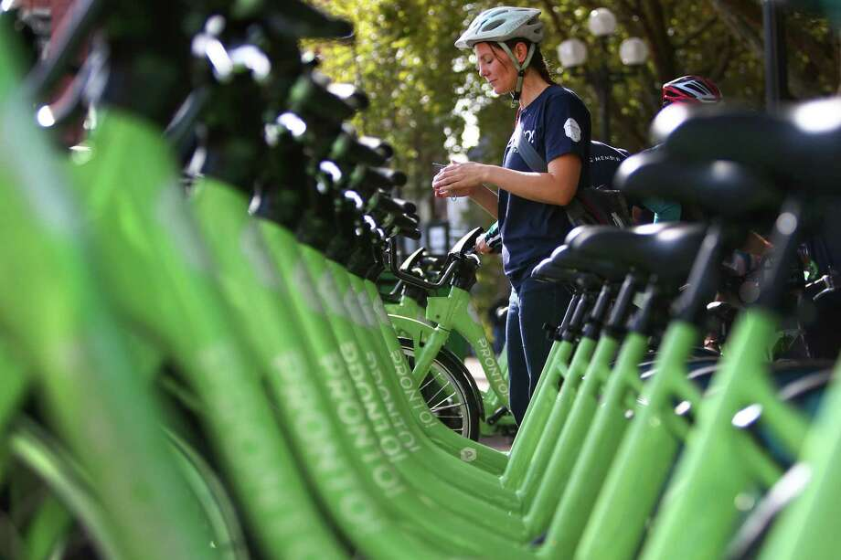A rider participating in an inaugural ride prepares to check out a bike from Pronto Cycle Share as the program is launched in Seattle on Monday, October 13, 2014. The program will have 500 bicycles available for rent at 50 stations mostly in the core of Seattle. Photo: JOSHUA TRUJILLO, SEATTLEPI.COM / SEATTLEPI.COM