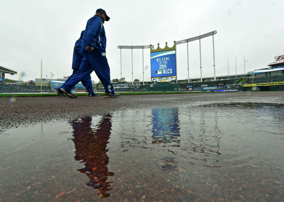 Royals grounds crew members pass a puddle at Kauffman Stadium, where rain postponed Game 3 of the ALCS. Photo: JOHN SLEEZER / McClatchy-Tribune News Service / Kansas City Star