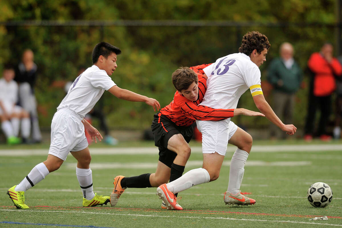 Ridgefield's Matteo Avellini is sandwiched in between Westhill's Charlie Teeters, left, and Ian Zacharewicz while trying to get to the ball during their soccer game at Westhill High School in Stamford, Conn., on Monday, Oct. 13, 2014. Ridgefield and Westhill played to a 2-2 tie.