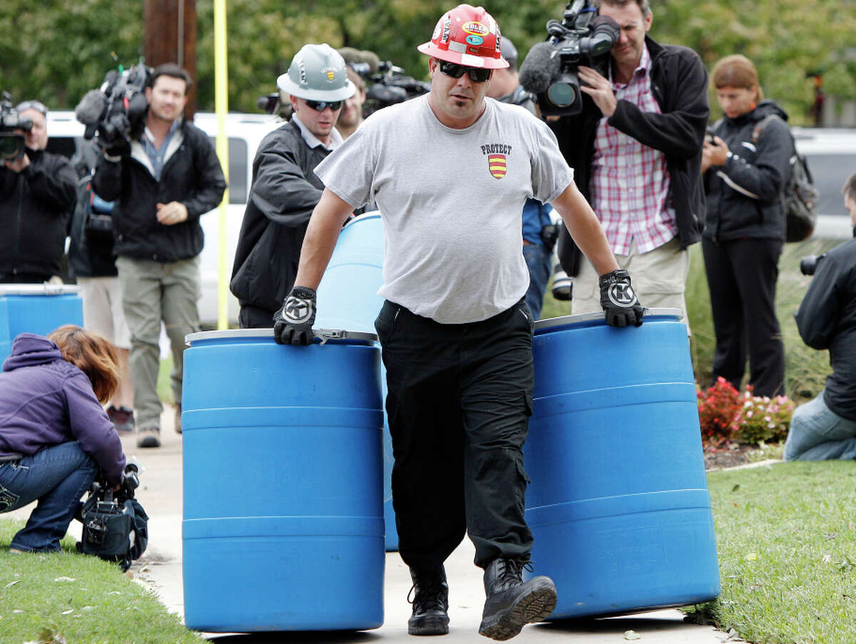 Workers move disposal barrels for disposing material outside the apartment of a health care worker who test positive for Ebola.