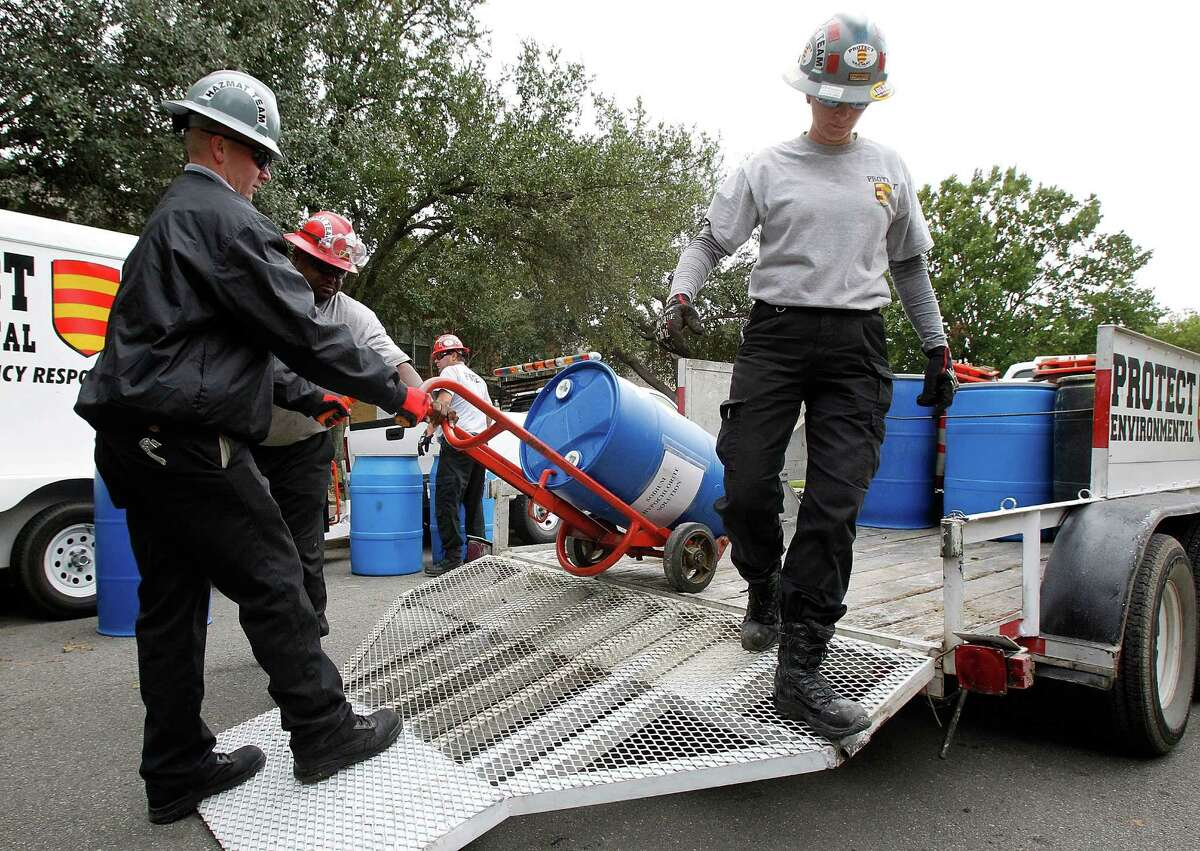 DALLAS, TX - OCTOBER 13: Hazmat workers unload a barrel labeled sodium hypocholorite solution from a trailer outside of an apartment where a second person diagnosed with the Ebola virus resides on October 13, 2014 in Dallas, Texas. Officials say a health care worker who cared for Liberian patient Thomas Eric Duncan has tested positive for the virus. (Photo by Mike Stone/Getty Images)