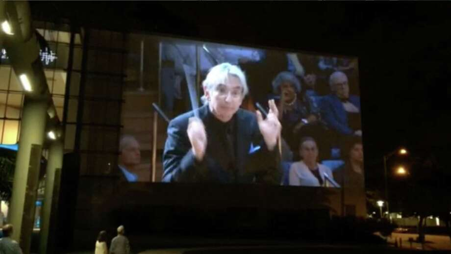 Michael Tilson Thomas conducts New World Symphony, in video broadcast on the side of the Gehry building.