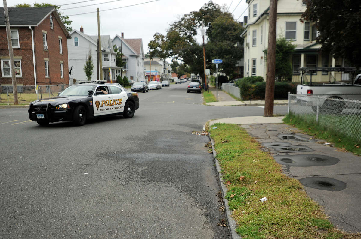 A Bridgeport police car passes the scene of the city's ninth homicide of the year at the corner of Pearl and Brook Streets on the city's east side on Monday, October 13, 2014.