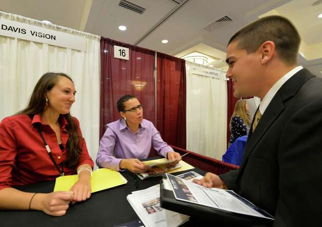 Representatives of Davis Vision; Nicole Diegel, recruiting, left, Diedre Pierson, customer service supervisor, center, speak with Brian Quenneville, right, at the Times Union October Job Fair Monday morning, Oct. 13, 2014, in Colonie, N.Y.    (Skip Dickstein/Times Union) Photo: SKIP DICKSTEIN / 10028983A