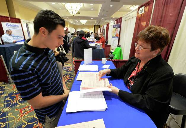 Andrew Bolton is speaks to Patty DiMento of the US Postal Service at the Times Union October Job Fair Monday morning, Oct. 13, 2014, in Colonie, N.Y.    (Skip Dickstein/Times Union) Photo: SKIP DICKSTEIN / 10028983A
