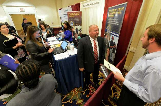 Dean Burke, Foreign Language supervisor for the FBI, left, speaks with Kevin Haskell, right, at the Times Union October Job Fair Monday morning, Oct. 13, 2014, in Colonie, N.Y.    (Skip Dickstein/Times Union) Photo: SKIP DICKSTEIN / 10028983A