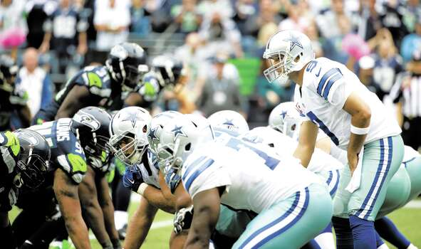 Dallas Cowboys players including quarterback Tony Romo, right, line up against the Seattle Seahawks on the line of scrimmage in the second half of an NFL football game, Sunday, Oct. 12, 2014, in Seattle. (AP Photo/Elaine Thompson) Photo: Elaine Thompson, Associated Press / AP