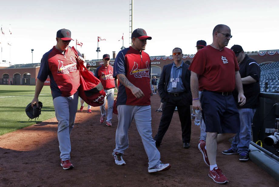 Cardinals catcher Yadier Molina (center), who left in the sixth inning of Sunday's game in intense pain, walks back to the locker room with teammates Monday at AT&T Park. Photo: Carlos Avila Gonzalez / The Chronicle / ONLINE_YES