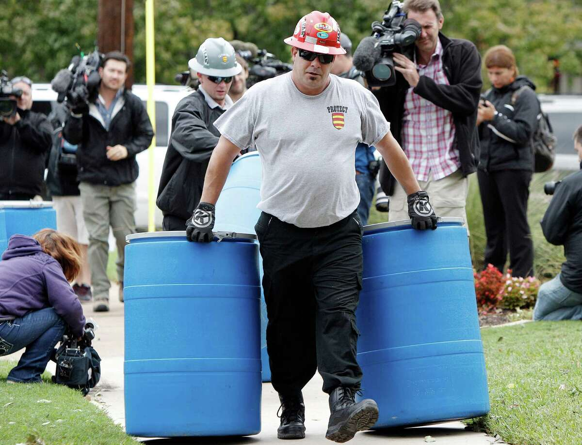 Protect Environmental workers move disposal barrels to a staging area outside the apartment of a healthcare worker who treated Ebola patient Thomas Eric Duncan and tested positive for the disease, Monday, Oct. 13, 2014, in Dallas. (AP Photo/Brandon Wade) ORG XMIT: TXBW112