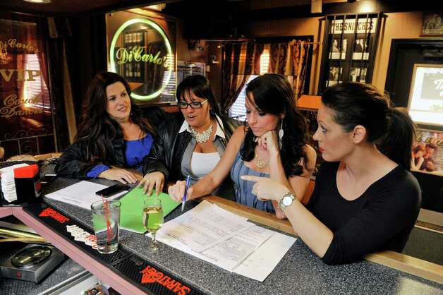 New co-owners of DiCarlo's Gentlemen's Club, Tess Collins, left, and Shy Abbasi, second from left, and the club's general manager, Chelsea Barraco, third from left and the club's manager Brandy Karczewski go over hiring and scheduling at the club on Sunday, Oct. 13, 2014, in Colonie, N.Y.   (Paul Buckowski / Times Union) Photo: Paul Buckowski / 10029013A