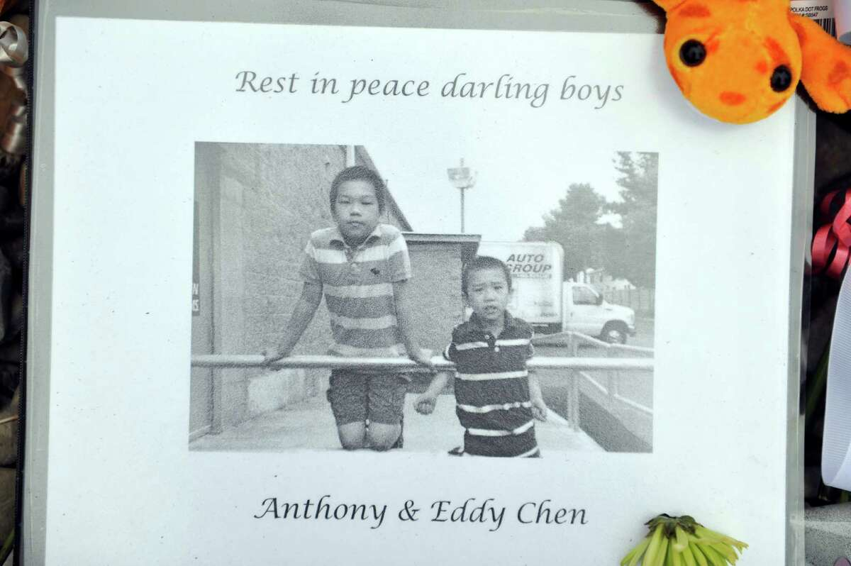 Flowers and other items have been left at the entrance to Guilderland Elementary School, along with a photograph of Anthony and Eddy Chen, seen here on Monday, Oct. 13, 2014, in Guilderland, N.Y. The two boys, Anthony, 10, and Eddy, 7, were found dead along with their parents Jin Chen, and Hai Yan Li last week in their home at 1846 Western Ave. in Guilderland, N.Y. The two boys went to school at Guilderland Elementary School. (Paul Buckowski / Times Union)