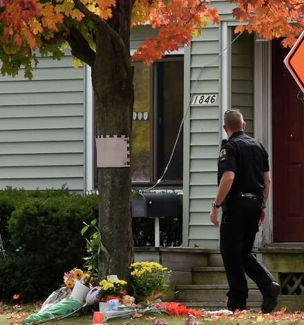 A Guilderland police officer walks past a makeshift memorial on the front lawn of of the quadruple homicide scene at 1846 Western Avenue Oct. 13, 2014 in Guilderland, N.Y. (Skip Dickstein/Times Union) Photo: SKIP DICKSTEIN
