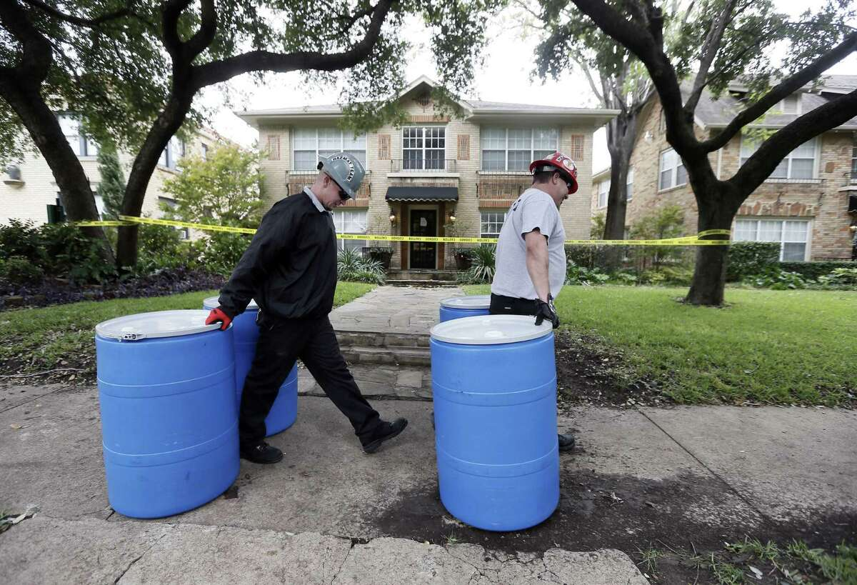 Protect Environmental workers move disposal barrels to a staging area outside the apartment of a health care worker who treated Ebola patient Thomas Eric Duncan and tested positive for it.