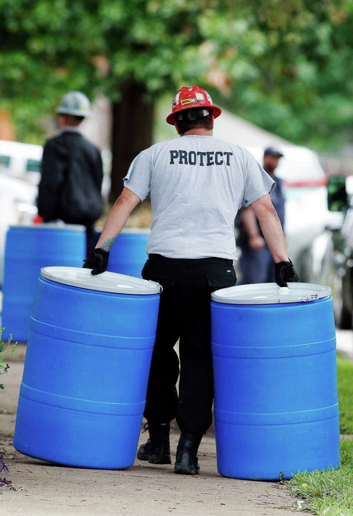 Environmental workers move disposal barrels from the Dallas apartment of a health-care worker who treated Ebola patient Thomas Eric Duncan.