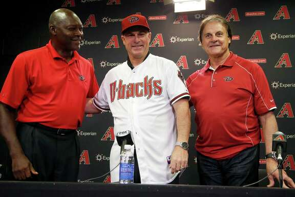 New Arizona Diamondbacks baseball team manager Chip Hale, middle, smiles as he is flanked by general manager Dave Stewart, left, and chief baseball officer Tony LaRussa during a news conference Monday, Oct. 13, 2014, in Phoenix.  The former Diamondbacks third base coach was hired Monday to replace fired  Kirk Gibson as the Diamondbacks manager.  The 49-year-old managed in Arizona's minor league system for six seasons and was with the Diamondbacks from 2007-09 in the first of eight consecutive seasons as a big league third base coach. (AP Photo/Ross D. Franklin)