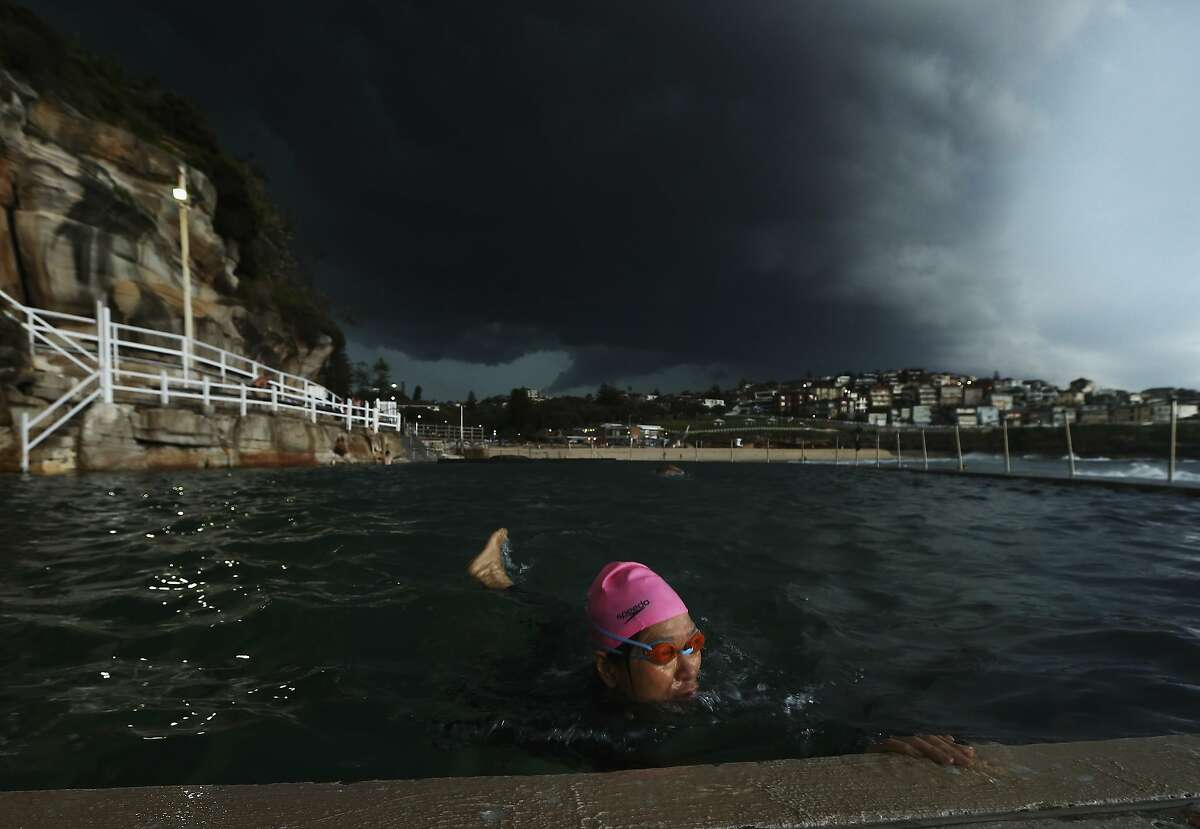 SYDNEY, AUSTRALIA - OCTOBER 13: A swimmer swims laps in Bronte Ocean Pool as a severe storm hits Sydney at Bronte Beach on October 13, 2014 in Sydney, Australia. (Photo by Ryan Pierse/Getty Images)
