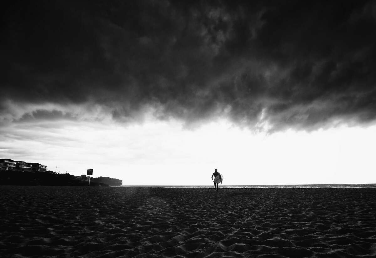 SYDNEY, AUSTRALIA - OCTOBER 13: (EDITORS NOTE: Image has been converted to black and white.) A surfer walks from the water as a severe storm hits Sydney at Bronte Beach on October 13, 2014 in Sydney, Australia. (Photo by Ryan Pierse/Getty Images)