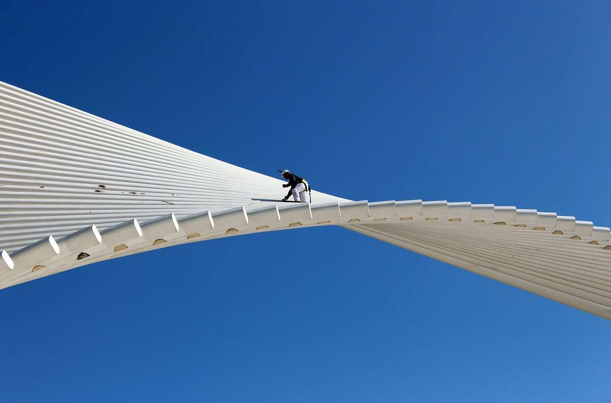 This Wednesday, October 1, 2014 photo shows Matt Radmacher, owner of Wisconsin Industrial Painters, as he walks along the wings above the Milwaukee Art Museum in Milwaukee, as part of a project to touch up the structure. Wisconsin Industrial Painters are touching up 40 rust spots on the Burke Brise Soleil, known as the wings, and repainting 72 plates. They started Sept. 29 and are expected to finish by the end of this week. This is only the second time the wings have needed touching up since opening in 2001. (AP Photo/Carrie Antlfinger)