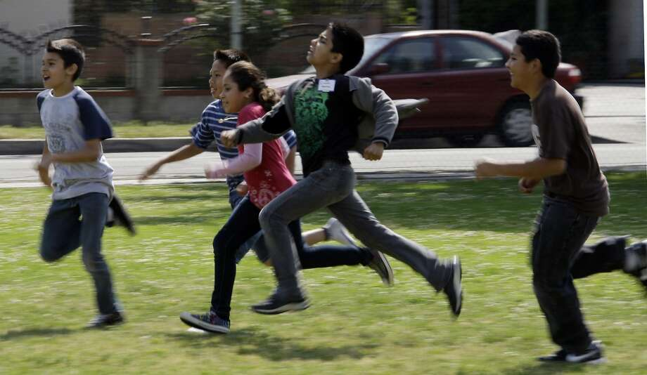 This May 10, 2011 file photo shows children at Tracy Elementary School running across a field as they take part in after-school exercise activities on the campus in Baldwin Park, Calif. Reading, writing, `rithmetic _ and PE?  The prestigious Institute of Medicine is recommending that schools provide opportunities for at least 60 minutes of physical activity each day for students and treat physical education as a core subject. The report says only about half of the nation's youngsters are getting at least an hour of vigorous or moderate physical activity every day. Photo: Reed Saxon, Associated Press