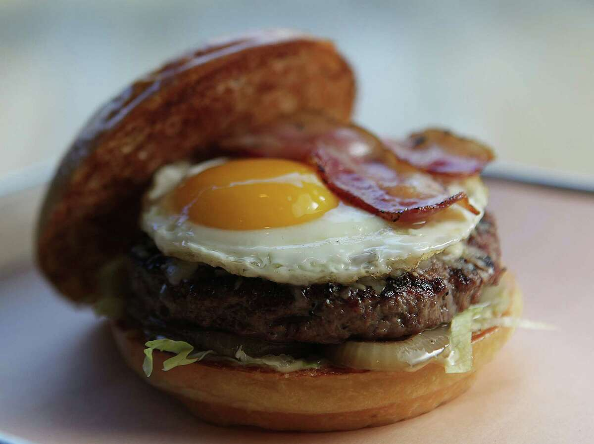 The Smoke burger ; house grilled bacon, aged Italian provolone, oven dried tomatoes, grilled onions, fried egg, truffle bacon mustard, lettuce, milk bun at Fielding's Wood Grill Monday, Dec. 16, 2013, in The Woodlands. ( James Nielsen / Houston Chronicle )