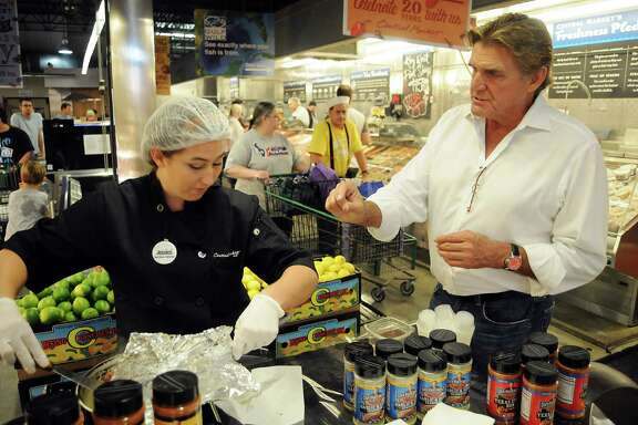Former Houston Oilers quarterback Dan Pastorini instructs Jessica Neeper during a cooking demonstration with his products last month at Central Market.