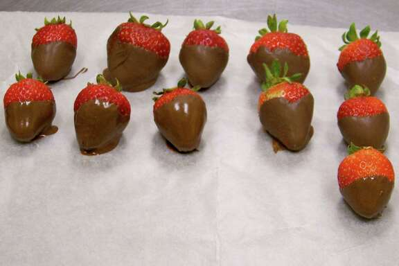 Lydia Mrzlak, culinary arts instructor at Lanier High School, demonstrates how to make chocolate-covered strawberries. She cleans the berries with a damp cloth, melts chocolate and dips them into a bowl of the melted chocolate.