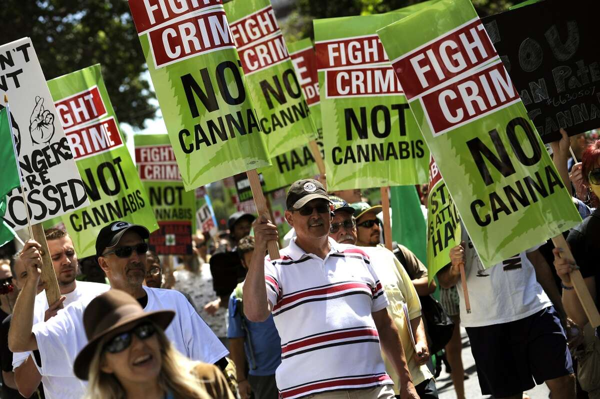 Supporters of medical marijuana march down Broadway in protest of President Obama who is giving a speech at the Fox Theater during a fundraising stop in downtown Oakland, CA Monday July 23rd, 2012