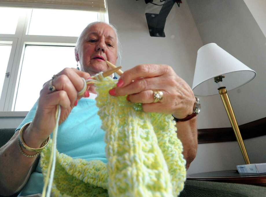 "Knitting volunteer, Judy Caravella of Cos Cob, knits a shawl prior to the celebration for the 2,000th shawl created and distributed to the Greenwich Hospital Oncology Department as part of the ""Healing Shawl"" program done by volunteers at Greenwich Hospital, Conn., Tuesday, Oct. 14, 2014. The 2000th shawl was done by Mary Fox of Greenwich who Betsy Corman, oncology volunteer coordinator for Greenwich Hospital, called,  ""flying fingers. Mary Fox is responsible for creating 197 shawls.""  Corman said there are 220 volunteers knitters who are a part of the program. Photo: Bob Luckey / Greenwich Time"