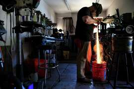 Sparks fly as master blade smith Aaron Wilburn grinds a knife blade at his home workshop on the outskirts of Redding.