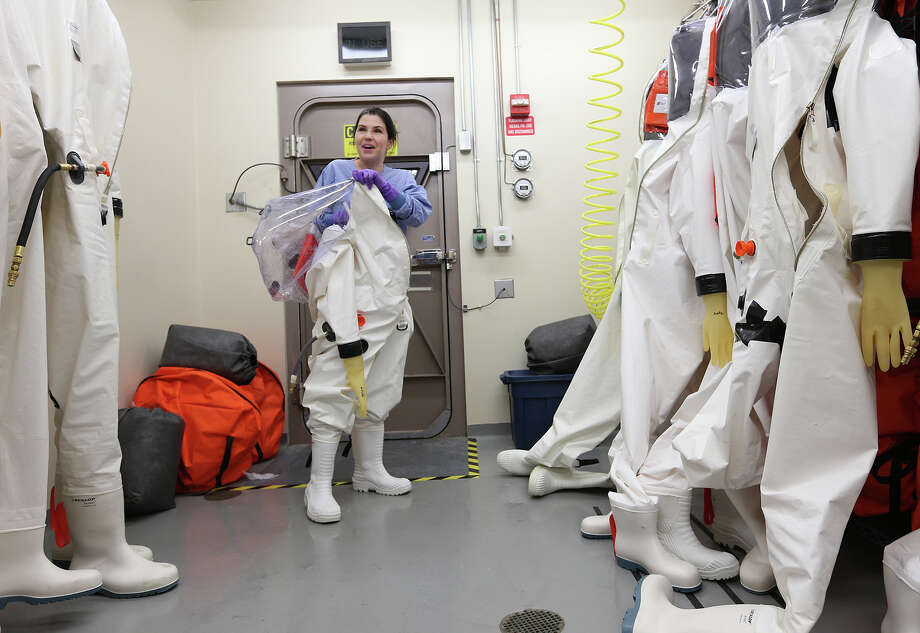 Researcher Dr. Gabi Worwa, DVM, removes her suit after working the with the Ebola virus in the Biosafety Level-4 lab of the Texas Biomedical Research Institute, Tuesday, Oct. 14, 2014. The institute has been working on an Ebola vaccine for the past 10 years. Photo: JERRY LARA, San Antonio Express-News / © 2014 San Antonio Express-News