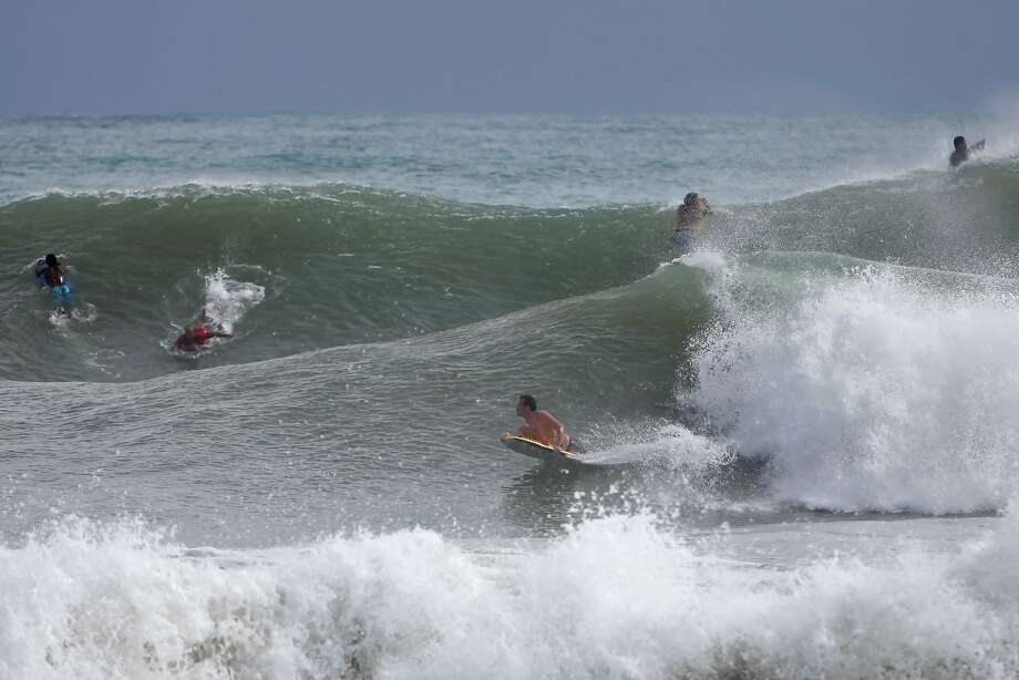 Surfers ride the waves in the waters at La Pared Beach in Luquillo, Puerto Rico, Tuesday, Oct. 14, 2014. Hurricane Gonzalo moved away from the area, but churned up heavy surf across much of the Caribbean, Tuesday. Forecasters said it could pick up strength and become a major storm as it approaches Bermuda. Photo: Ricardo Arduengo, Associated Press