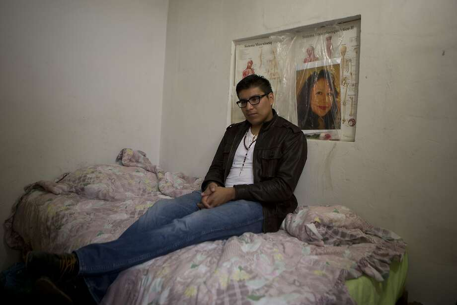 In this Friday, Oct. 3, 2014 photo, Dario Guerrero sits for a portrait in his bedroom with a picture of his late mother, at his grandparents' home on the outskirts of Mexico City. Guerrero, a Harvard University junior, accompanied his dying mother to Mexico without government permission, and is now unable to return to the United States. Photo: Dario Lopez-Mills, Associated Press